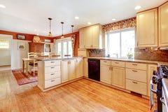 Stanza semplice della cucina di colori caldi con una piccola area pranzante Immagine Stock
