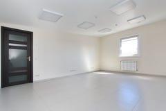 Stanza vuota interna della luce dell'ufficio con la carta da parati bianca non ammobiliata in una nuova costruzione immagine stock