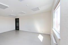 Stanza vuota interna della luce dell'ufficio con la carta da parati bianca non ammobiliata in una nuova costruzione fotografia stock