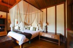 Stanze d'annata del letto nell'hotel o nella località di soggiorno Fotografia Stock