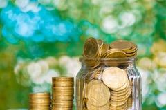 Stap van muntstukkenstapels en gouden muntstukgeld in de glaskruik op lusje Royalty-vrije Stock Afbeelding