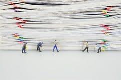 Stapelüberlastungspapier und Miniaturleuten werden es zerstört lizenzfreie stockbilder