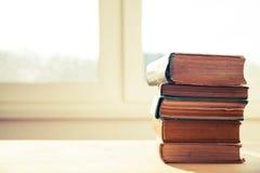 Stapel alte Bücher auf hölzernem Schreibtisch Stockfoto