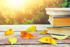 Stapel alte Bücher auf Holztisch draußen am Nachmittag Stockfoto