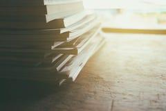 Stapel alte Bücher auf Holztisch mit hellem Leck Stockbilder