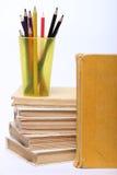 Stapel alte Bücher Bleistifte in einem Glas Stockbild
