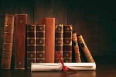 Stapel alte Bücher mit Diplom auf Schreibtisch Stockbild