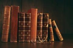 Stapel alte Bücher mit Gläsern auf Schreibtisch Stockbild