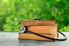 Stapel alte Bücher mit Stethoskop auf Holztisch Stockfotografie