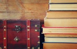 Stapel alte Bücher nahe bei antikem hölzernem Kasten auf hölzernem Regal Weinlese gefiltert Stockbilder