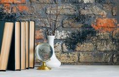 Stapel alte Bücher, Niederlassungen im Vase, Glaskugel, Schmutzziegelstein Stockfotografie