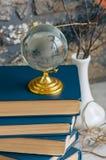 Stapel alte Bücher, Niederlassungen im Vase, Glaskugel, Schmutzziegelstein Stockfotos