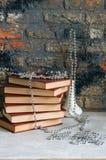 Stapel alte Bücher, Niederlassungen im Vase mit Girlande, Ziegelstein backgro Lizenzfreie Stockbilder