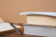 Stapel alte Bücher, Notizbuch, öffnete Buch mit Stift auf hölzernem Vorsprung Stockfotografie