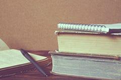 Stapel alte Bücher, Notizbuch, öffnete Buch mit Stift auf hölzernem Vorsprung Lizenzfreies Stockfoto