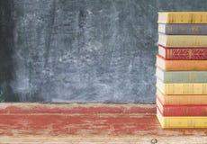 Stapel alte Bücher, vor einem schwarzen Brett Stockfotografie