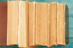 Stapel alte und benutzte Bücher oder Lehrbücher des gebundenen Buches auf blauem woode Lizenzfreies Stockbild