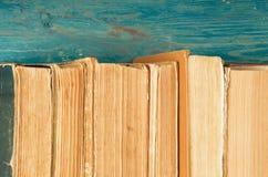 Stapel alte und benutzte Bücher oder Lehrbücher des gebundenen Buches auf blauem woode Lizenzfreie Stockbilder