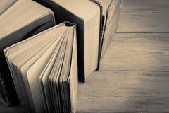 Stapel alte und benutzte Bücher oder Lehrbücher des gebundenen Buches auf hölzernem BAC Stockbilder