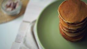 Stapel Amerikaanse pannekoeken op groene plaat op keukenlijst Pannekoekontbijt stock videobeelden