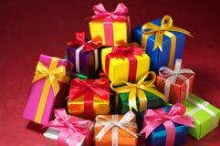 Stapel av lilla gåvor på röd bakgrund. arkivfoto