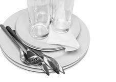 Stapel av vita plattor, exponeringsglas, gafflar, skedar. Royaltyfri Fotografi