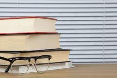 Stapel Bücher auf einer Tabelle mit Augengläsern Stockfotografie