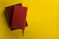 Stapel Bücher des gebundenen Buches, Tagebuch auf hölzerner Plattformtabelle und gelber Hintergrund Zurück zu Schule Kopieren Sie Stockfotos