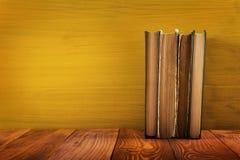 Stapel Bücher des gebundenen Buches, Tagebuch auf hölzerner Plattformtabelle und gelber Hintergrund Zurück zu Schule Kopieren Sie Lizenzfreie Stockfotos