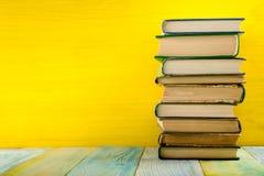 Stapel Bücher des gebundenen Buches, Tagebuch auf hölzerner Plattformtabelle und gelber Hintergrund Zurück zu Schule Kopieren Sie Lizenzfreie Stockfotografie