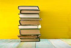 Stapel Bücher des gebundenen Buches, Tagebuch auf hölzerner Plattformtabelle und gelber Hintergrund Zurück zu Schule Kopieren Sie Stockfoto