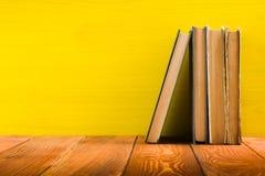 Stapel Bücher des gebundenen Buches, Tagebuch auf hölzerner Plattformtabelle und gelber Hintergrund Zurück zu Schule Kopieren Sie Stockbild
