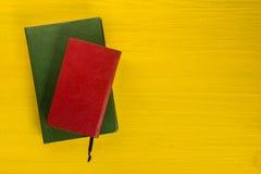 Stapel Bücher des gebundenen Buches, Tagebuch auf hölzerner Plattformtabelle und gelber Hintergrund Zurück zu Schule Kopieren Sie Lizenzfreies Stockfoto