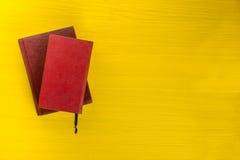 Stapel Bücher des gebundenen Buches, Tagebuch auf hölzerner Plattformtabelle und gelber Hintergrund Zurück zu Schule Kopieren Sie Stockfotografie