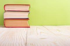 Stapel Bücher des gebundenen Buches, Tagebuch auf hölzerner Plattformtabelle und grüner Hintergrund Zurück zu Schule Kopieren Sie Stockfotos