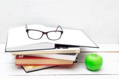 Stapel Bücher für Studie und ein grüner Apfel auf einem weißen Hintergrund Lizenzfreie Stockfotografie