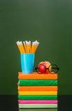 Stapel Bücher mit Apfel und Bleistifte nähern sich leerer grüner Tafel Lizenzfreies Stockbild