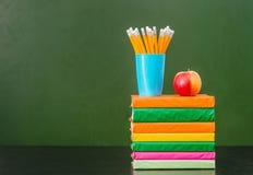 Stapel Bücher mit Apfel und Bleistifte nähern sich leerer grüner Tafel Stockfoto