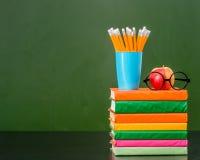 Stapel Bücher mit Apfel und Bleistifte nähern sich leerer grüner Tafel Stockbilder