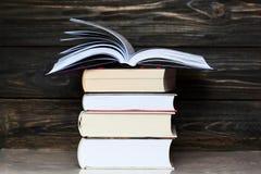 Stapel Bücher mit dunklem hölzernem Hintergrund Ein Buch ist geöffnet Stockbild