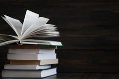 Stapel Bücher mit dunklem hölzernem Hintergrund Ein Buch ist geöffnet Stockfoto