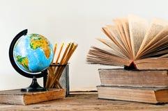 Stapel Bücher mit einer Kugel und einem Bleistift Lizenzfreie Stockfotos