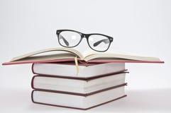 Stapel Bücher mit geöffnetem Notizbuch und Gläsern Lizenzfreie Stockbilder