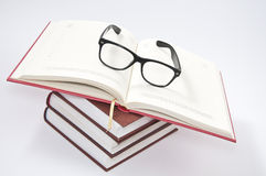 Stapel Bücher mit geöffnetem Notizbuch und Gläsern Stockbild