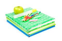 Stapel Bücher mit Schule suppley und grünem Apfel Lizenzfreie Stockbilder