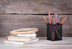 Stapel Bücher und Bleistifte auf dem Holztisch Lizenzfreie Stockfotos