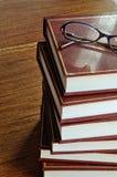 Stapel Bücher und Gläser auf tablel horizontalem Bild lizenzfreie stockfotografie