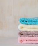 Stapel Badetücher auf heller hölzerner Hintergrundnahaufnahme Stockfotografie