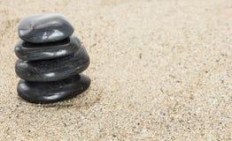 Stapel balancierende Steine des schwarzen Basalts auf Sand Stockbilder