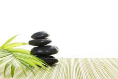Stapel balancierende Steine des schwarzen Basalts mit grünem Blatt auf Bambusmatte, auf weißem Hintergrund Lizenzfreie Stockfotos